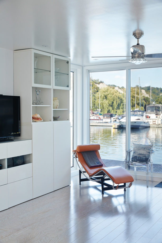 Sliding glass from Canada Windows & Doors maximizes Cheung and Cauldwell's views of the marina. LC4 Chaise available at DWR; cabinets from IKEA.