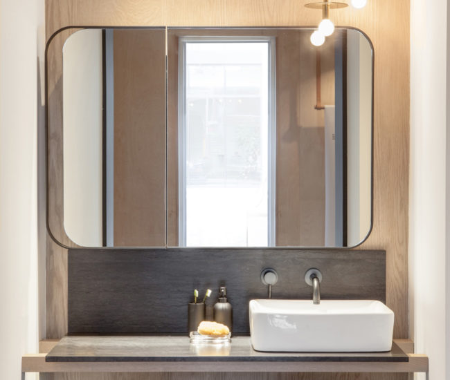 Behind the custom vanity and metal-framed mirror, a woodgrain Stone Tile wall treatment mimics the look of barnboard. Photo by Scott Norsworthy.