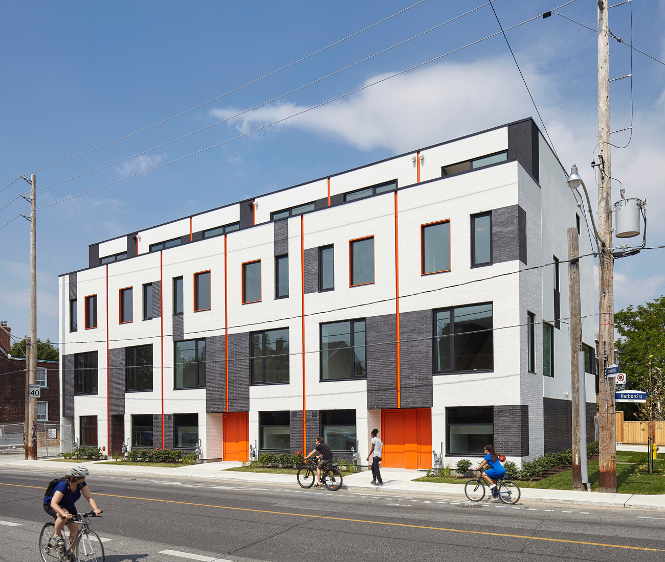 Grey and white brick and orange finishes make Superkül's design hard to miss. To reduce waste and save time, the project was built on-site using prefabricated frames. Photo by Ben Rahn.
