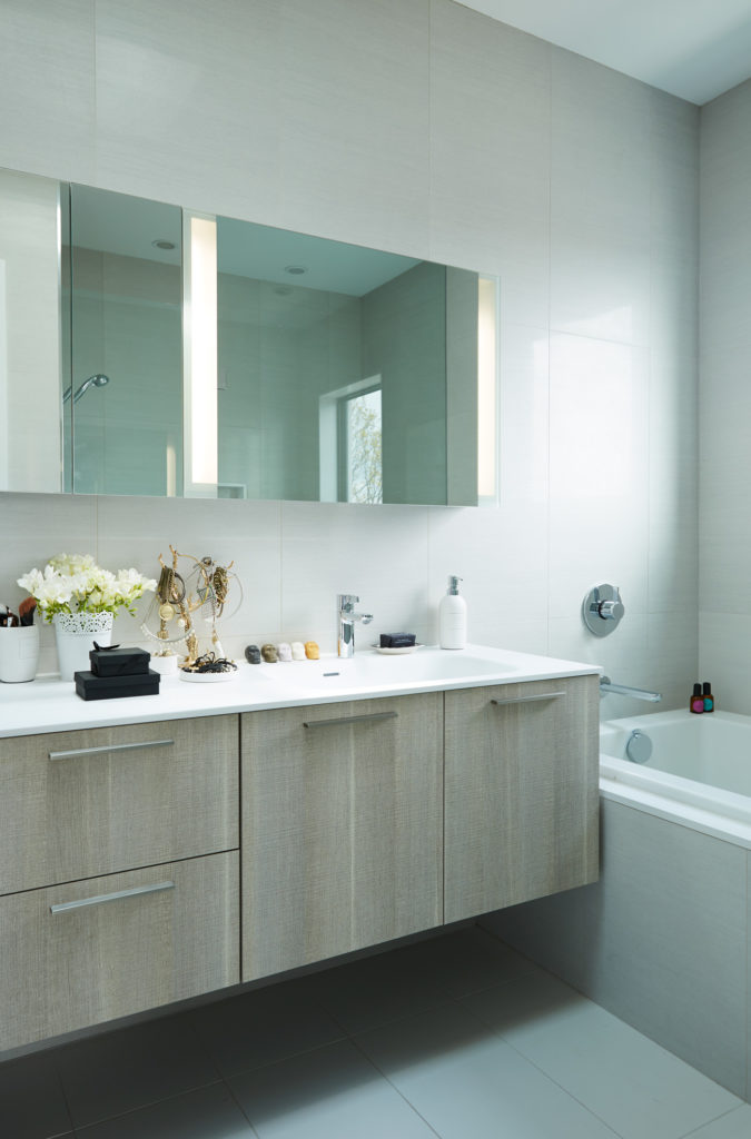 On the third floor, a skylight-lit Scavolini en suite fits a double sink, a skirted tub, shower and water closet. Toiletries from Art 27; porcelain from Stone Tile. Photo by Naomi Finlay.