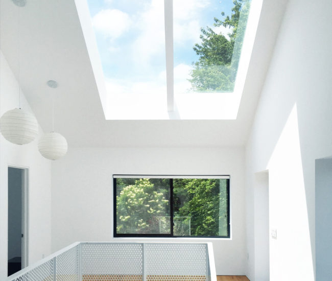In the nearly eight-metre-tall atrium, a perforated-steel staircase by Cobalt Fabrication connects the two storeys. Skylights by Artistic; Noguchi pendants at Quasi Modo.