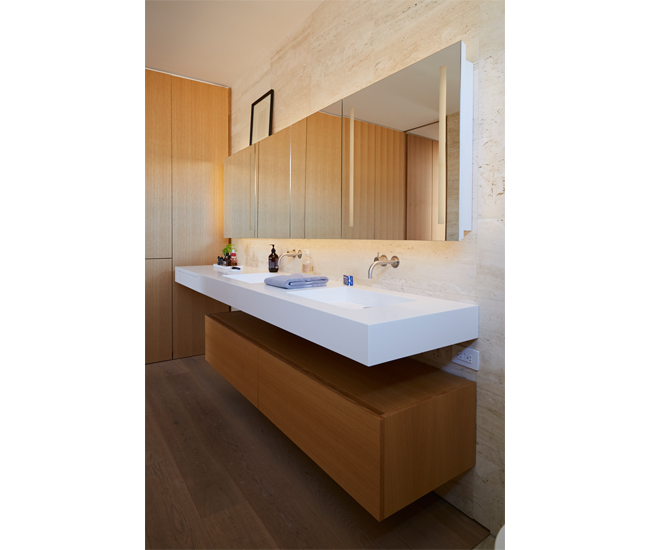 1 Don't be afraid to mix wood and stone. Travertine finishes from Marble Trend. Engineered white oak flooring. A Corian vanity floats above cabinetry by O'Sullivan Millwork. Photo by Naomi Finlay.