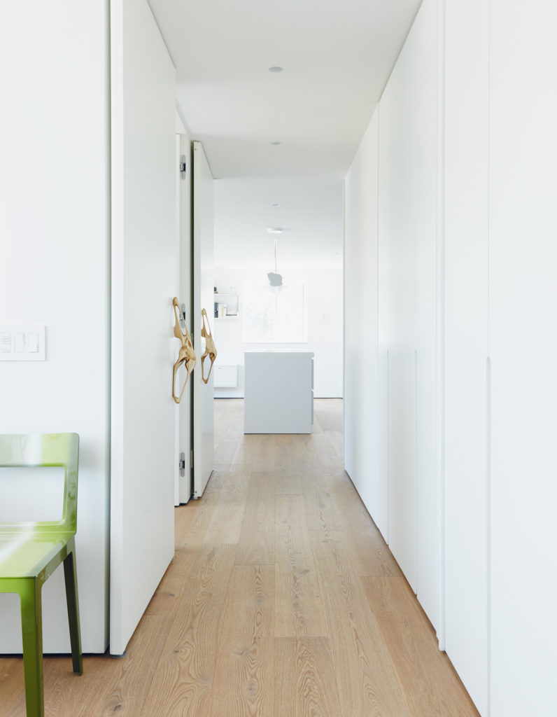 Six metres of millwork by MCM conceals a family's worth of stuff while space-saving sliding doors offer privacy. Photo by Michael Graydon.