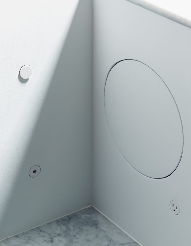 Coin-sized power outlets by Bocci and circular HVAC access panels. Photo by Michael Graydon.