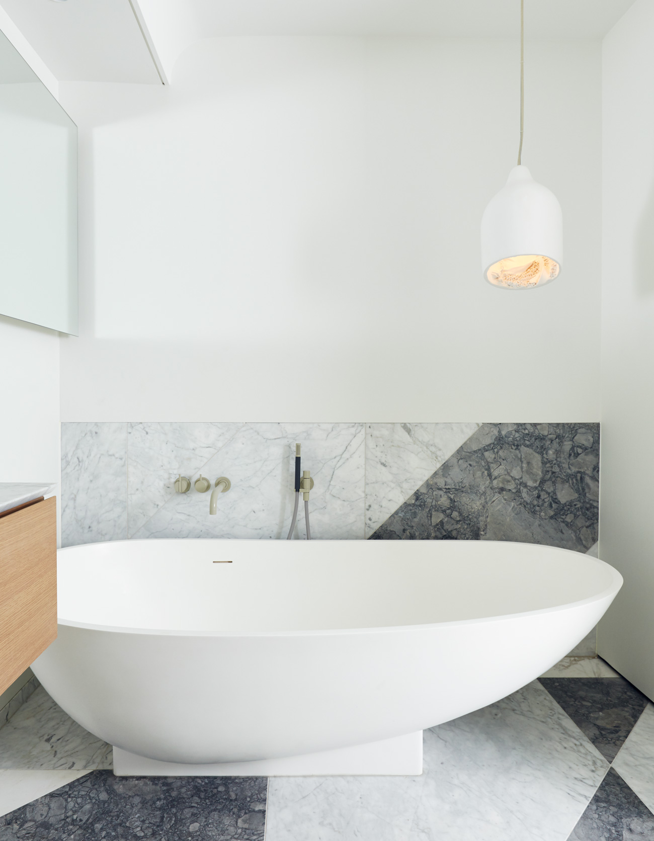 Flooring and backsplash were fashioned from York Fabrica marble off-cuts. Tub and faucets from Ginger's. Photo by Michael Graydon.