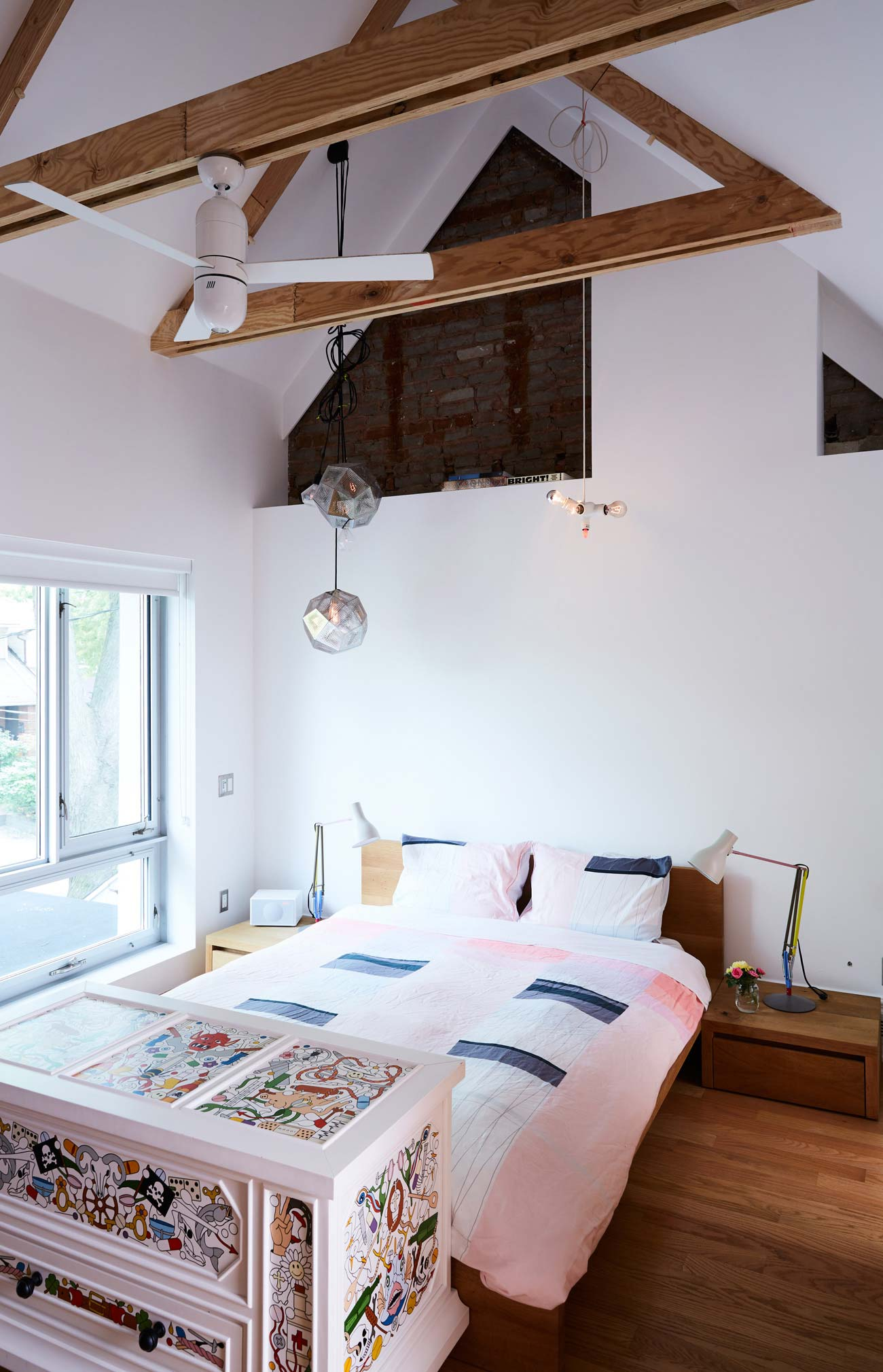Trusses frame the peak in the master. At the foot of the bed is a Moooi trunk from Klaus.