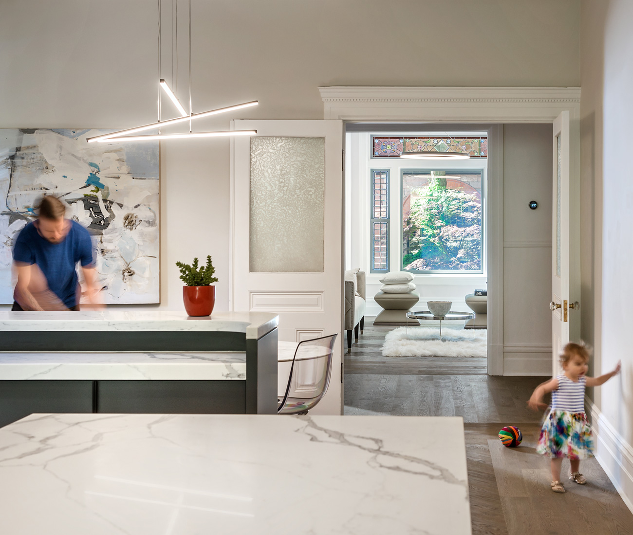 Book-matched quartzite on the island and backsplash lends the contemporary kitchen timeless appeal. Light from Sescolite; art by Rachel Ovadia.