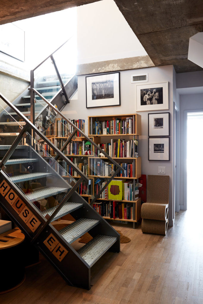 The foyer's steel staircase rises next to art books on shelving from Urban Mode and Gehry's cardboard Wiggle side chair for Vitra from ShopAGO.