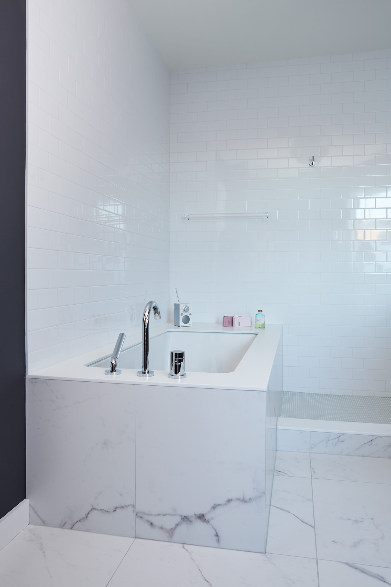 A thin slice of Corian from Surfacing Solutions tops the Neptune tub – it's clad with porcelain to blend with the floor. Subway tiles from Stone Tile.