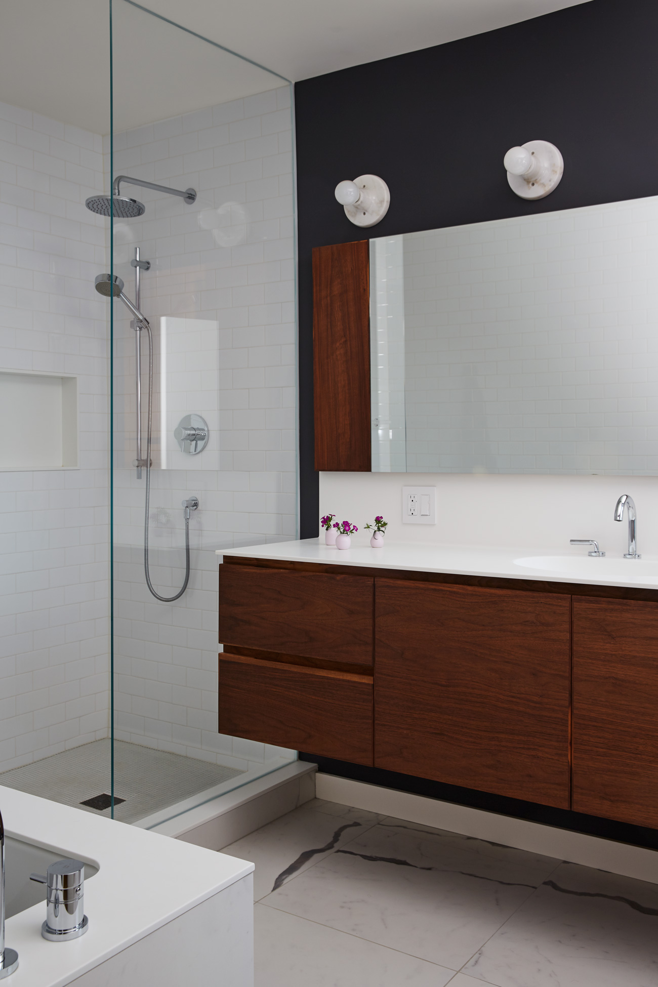 The bath's focal wall plays up the veins in the porcelain (from Stone Tile). A custom mirror from CGA Glass accents Lynn's Corian-topped walnut vanity.