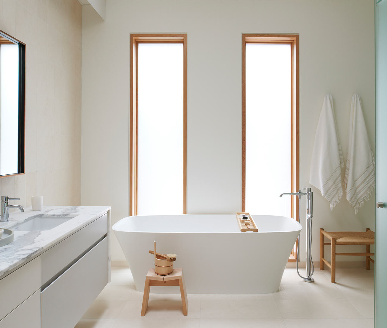 Stone Tile limestone runs from the floor up behind the vanity. Mjölk accessories echo the mahogany trim around the windows. Photo by Alex Lukey.