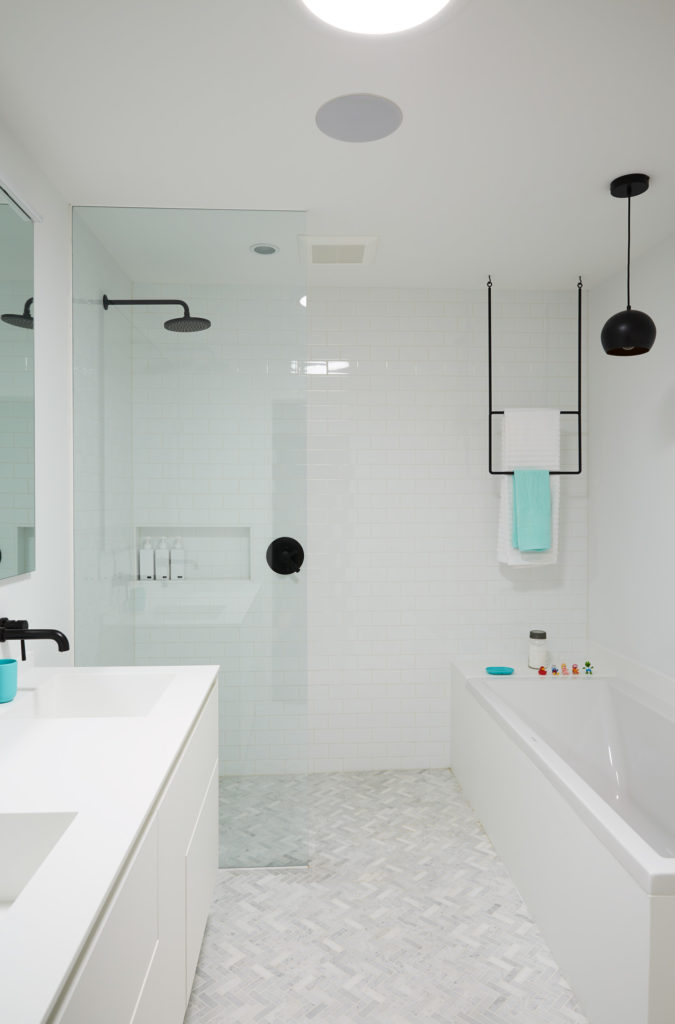 Black fixtures and an MDT Mobilier towel rack add punch to the all-white family bath. Accessories from Umbra; Flooring from Stone Tile; showerhead by Brizo.