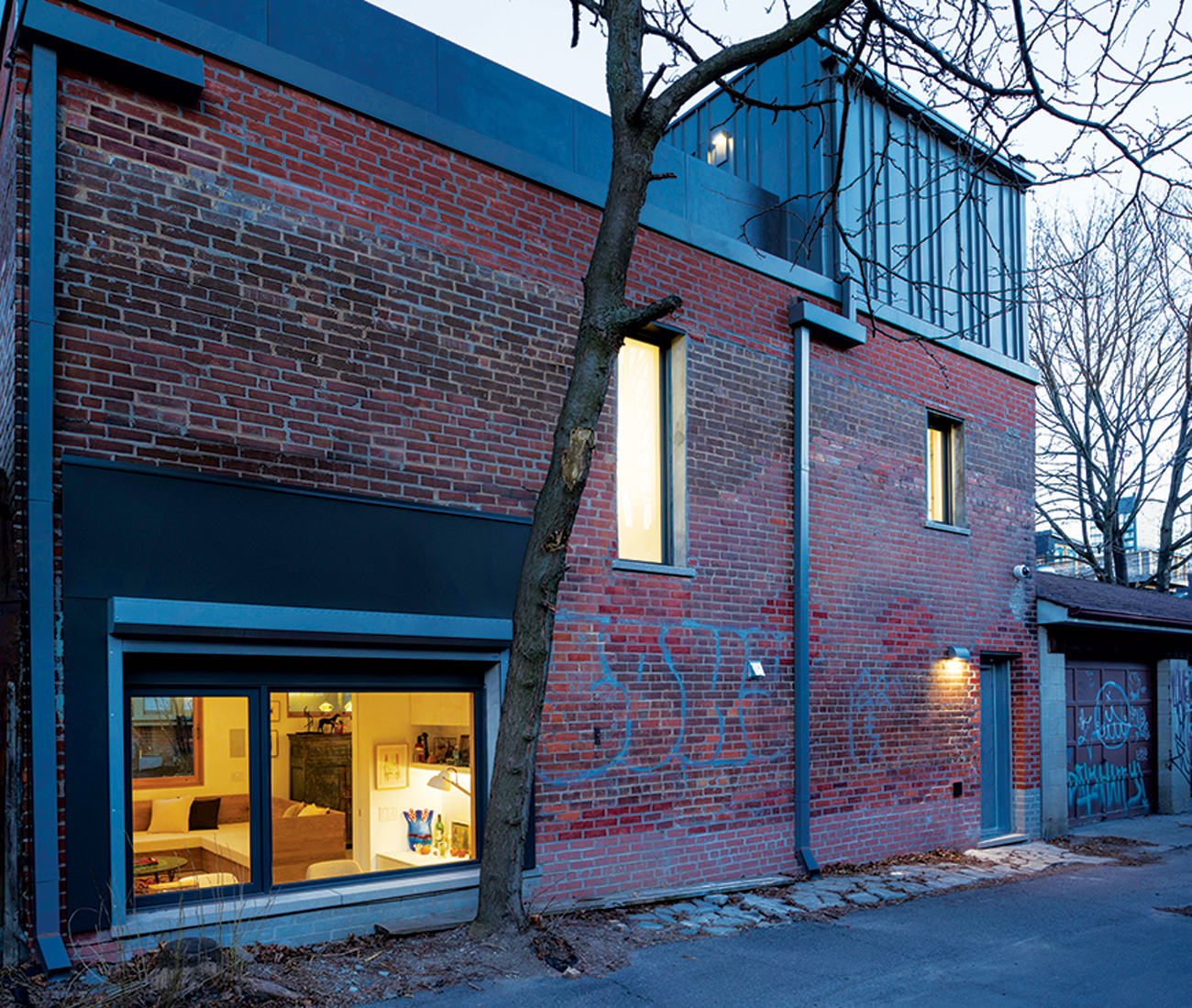 Original brick was reused to rebuild the structure, which is now topped with zinc roof flashing and eaves. A Nice For You shutter secures the office window at the push of a button.