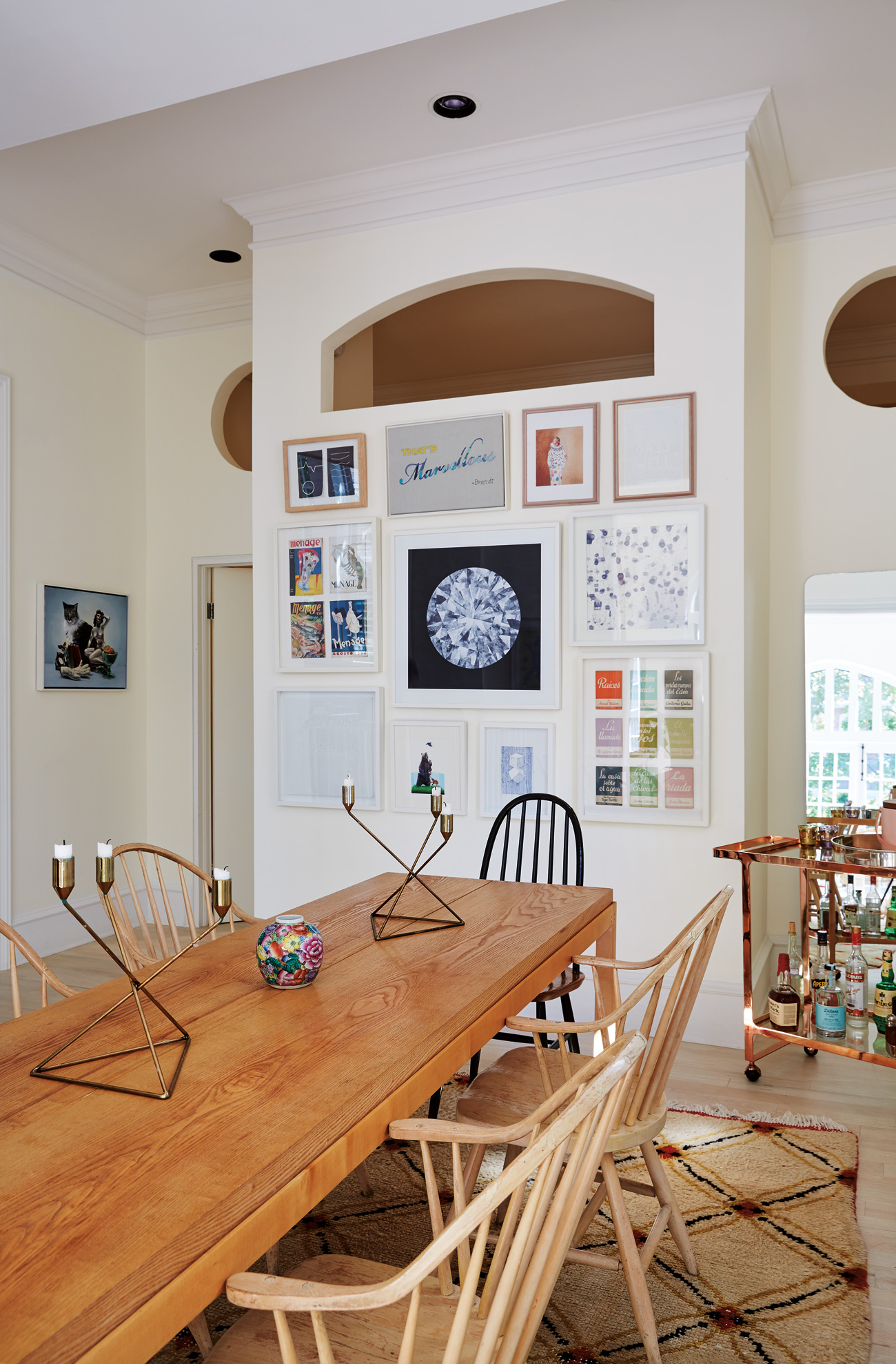 Cutouts – remnants of the '90s conversion from rectory to condo – draw southern light into the master bedroom. Dining table from Barny Lee; bar cart from CB2; rug is a street score.