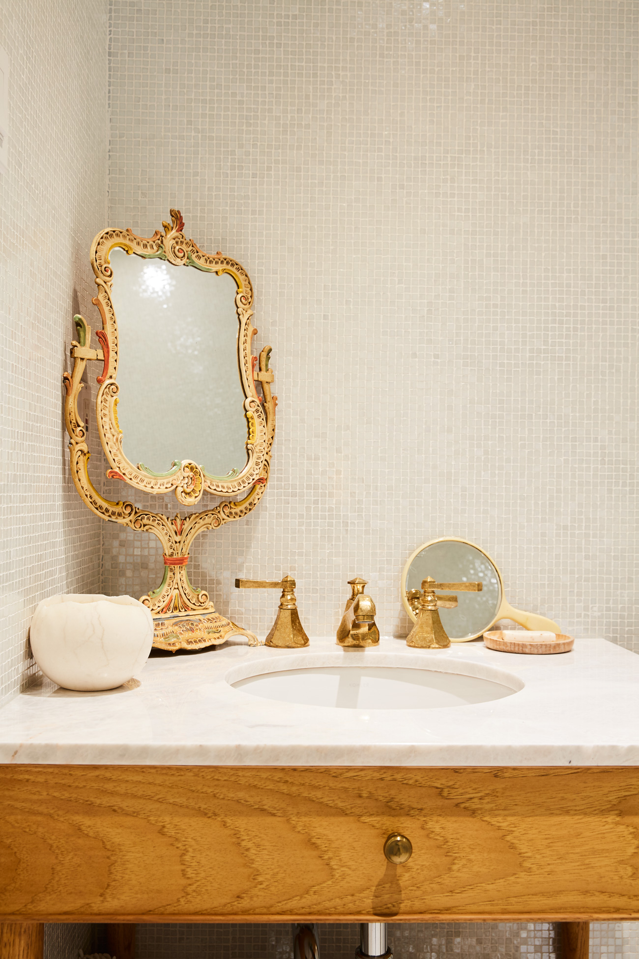 In the guest bath, Ginger paired a mosaic by Ceragres with porcelain flooring from Stone Tile. Vintage mirror; faucet from Roman Bath.