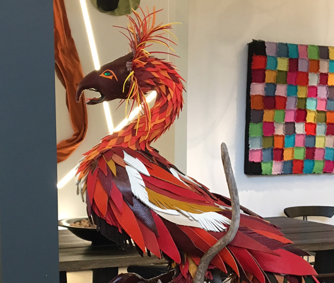 Phoenix Rising. This roosted phoenix by Susan Taylor caught our eye, not only because of it's eye-catching colour, but because its fiery plumage is made entirely from discarded pieces of leather, plastic rhinestones, and felt. The metaphor - of a bird rising from a pile of obsolete material - made an impact on us. (Dark Tools, 750 Lake Shore Blvd E.)