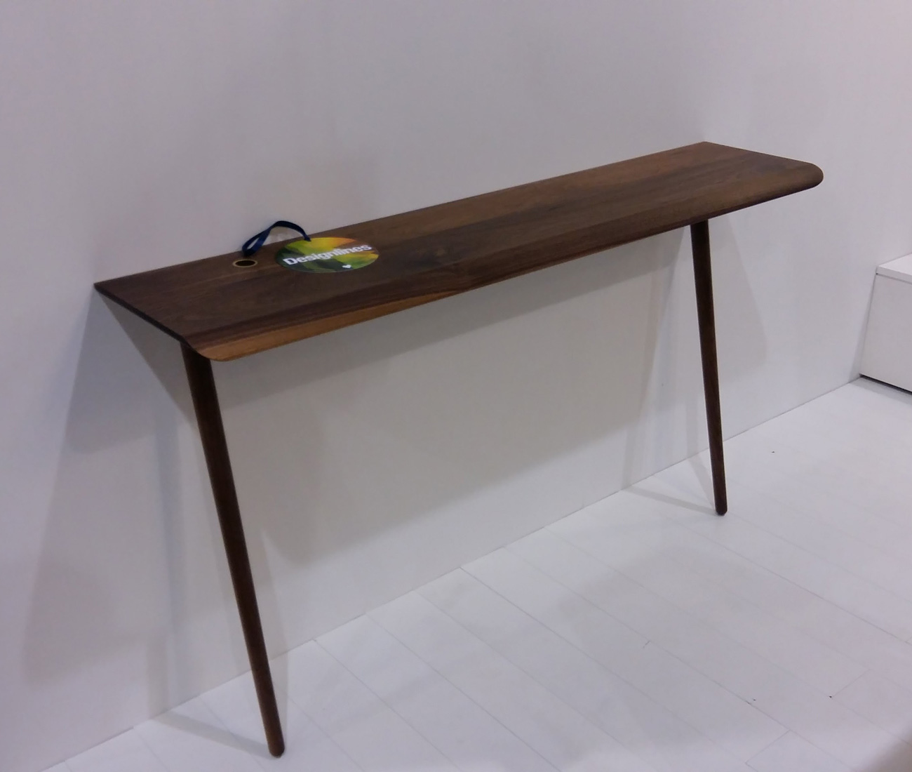 T406 by Kastella. Love the compact footprint of this walnut leaning desk and the combination of the impeccable traditional craftsmenship with the subtle digital world disruption of the metal eyelet for cords and cables. A perfect perch for a laptop, or it would make a great console table.