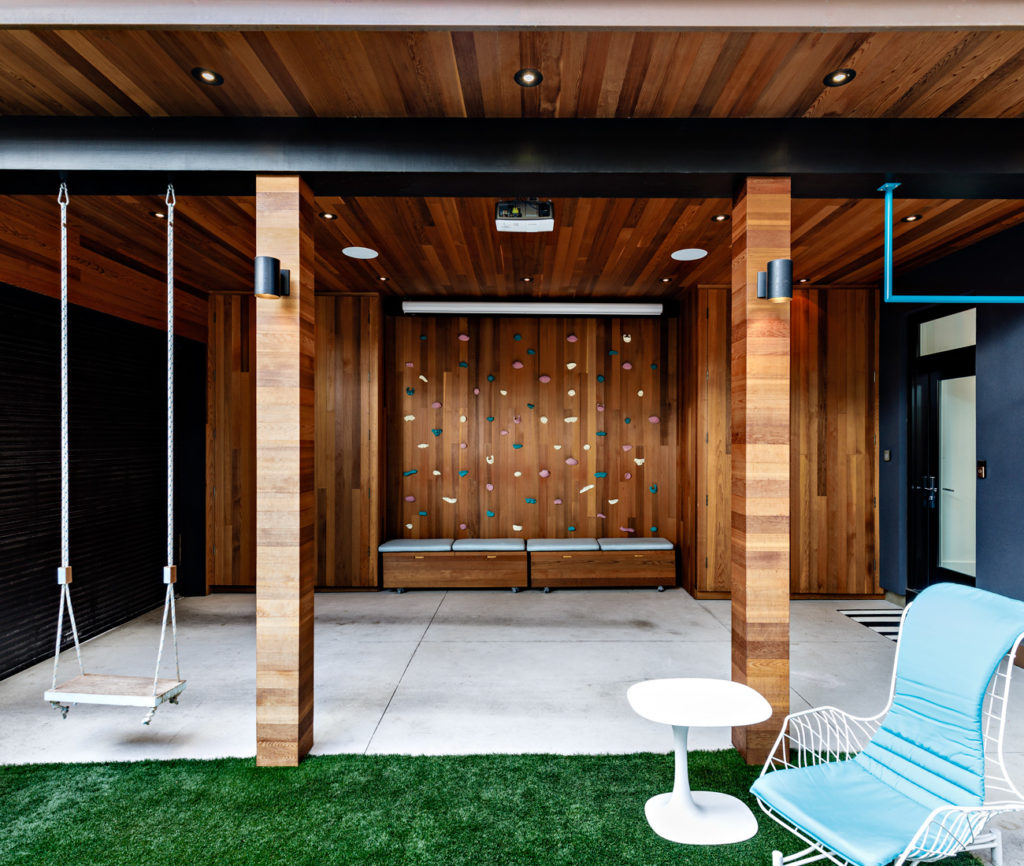 Sheltered by the cedar-clad carport is a climbing wall and, above this, a projection screen for backyard movie nights with friends.