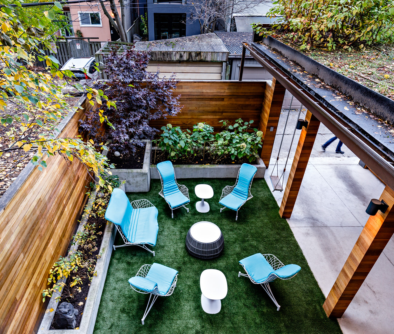 The master bedroom overlooks a planted rooftop and the west-facing backyard, where artificial turf and concrete planters make for the perfect, family-friendly urban retreat. Outdoor furniture by Oasiq.