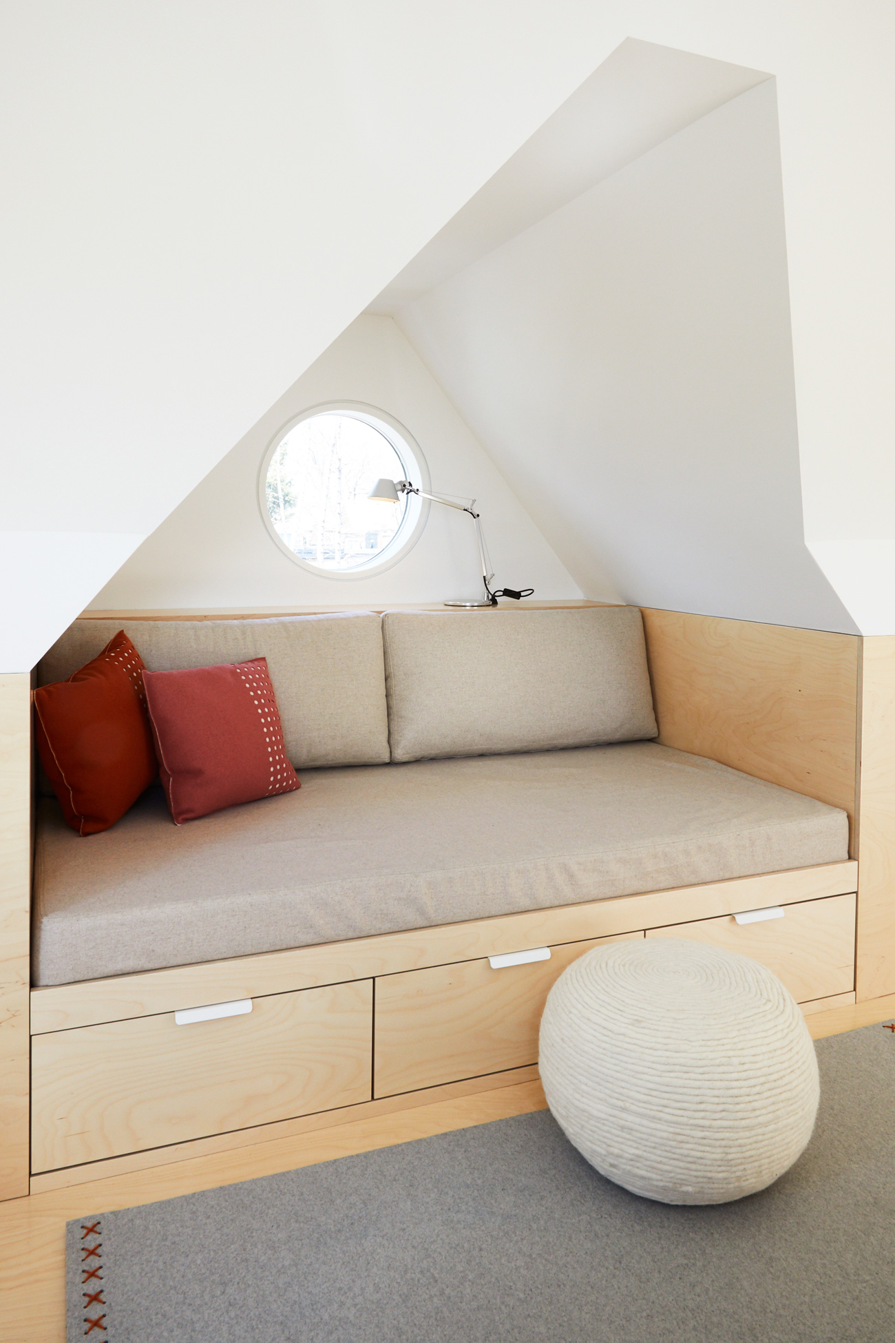 The attic was finished with pale, neutral-toned upholstery and blonde wood reminiscent of a treehouse.