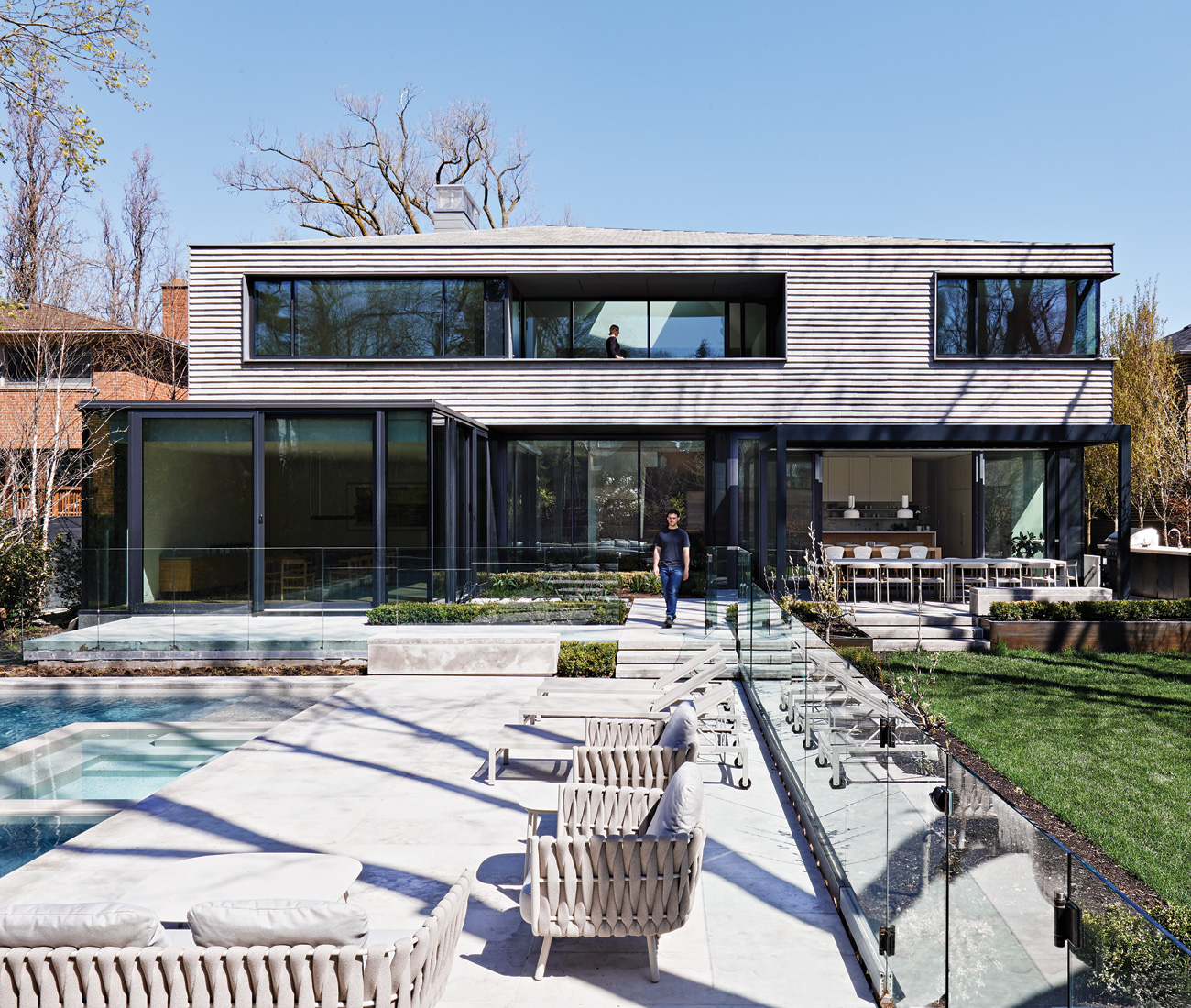 The back of the home reveals its hipped-roof design and upper walkout. Build by Mazenga; landscaping by Fox Whyte; Tribù furniture from Avenue Road.