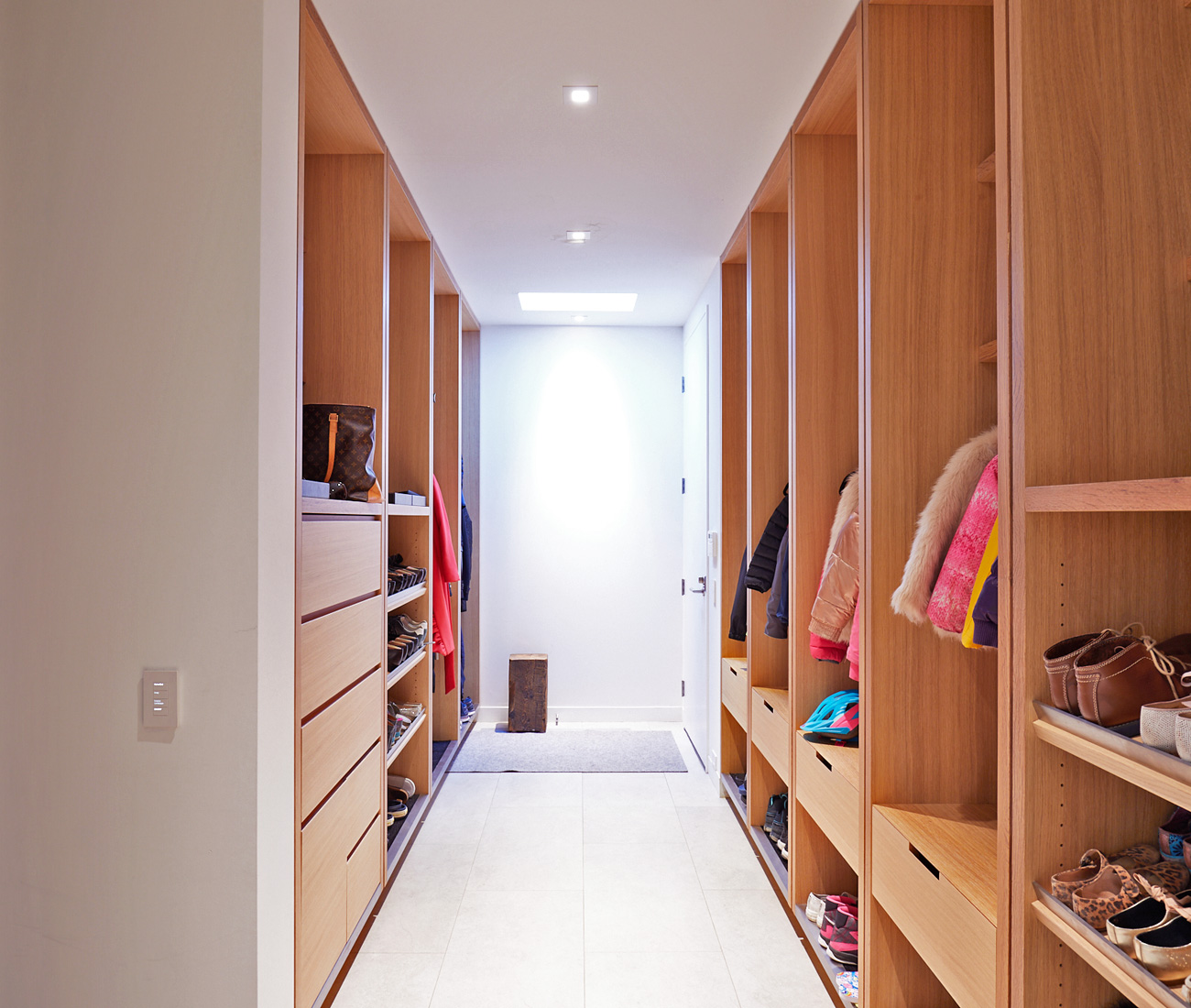 "Ceiling-height ""lockers"" in white oak provide storage for the family of six. Millwork by Mar-Tec Woodworking."