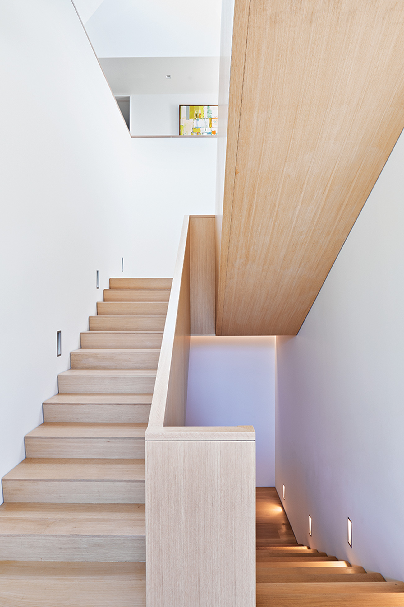 The wide switch-back staircase, built by Erik Cabinets using white oak, spans three storeys.