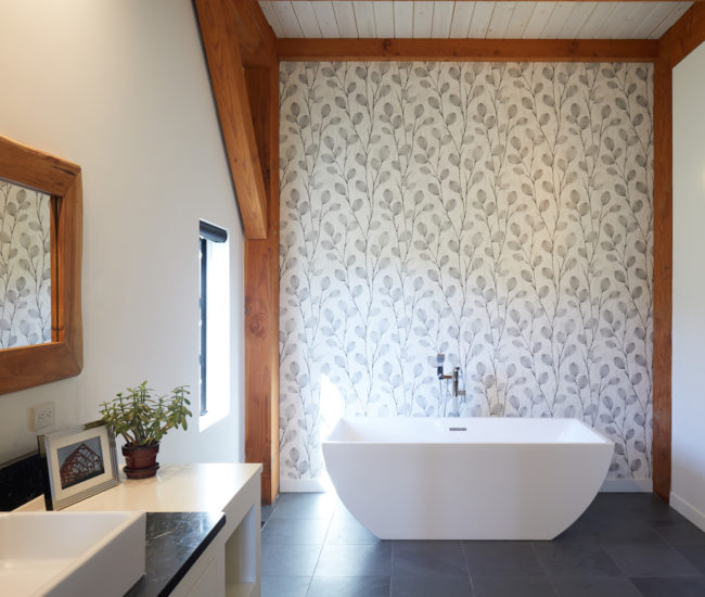 Beyond the barn door is the master suite, where a vintage teak bed, plus Crown Wallpaper and a soaker tub in the bathroom, take centre stage.