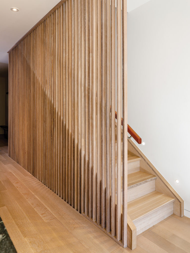 The solid oak staircase features slatted balusters and slip-resistant grooves.