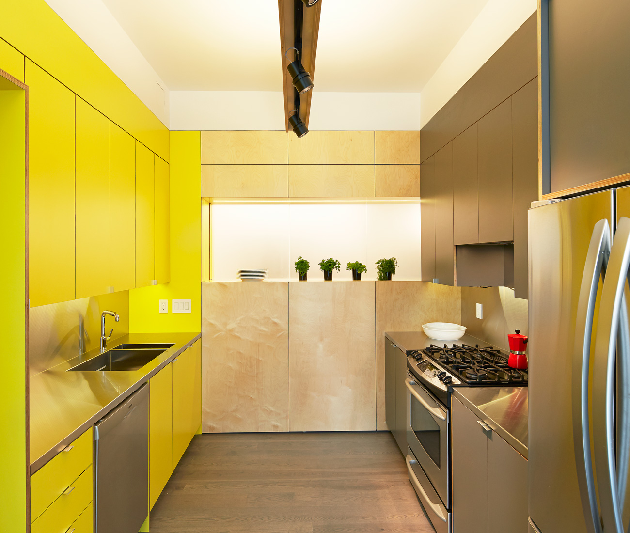 Yellow cabinetry incorporates a backlit neon art piece by Orest Tataryn. Engineered white oak flooring by Baltic Wood, chair by B&B Italia and resin vase by Gaetano Pesce, courtesy of Studio Pazo, Toronto.