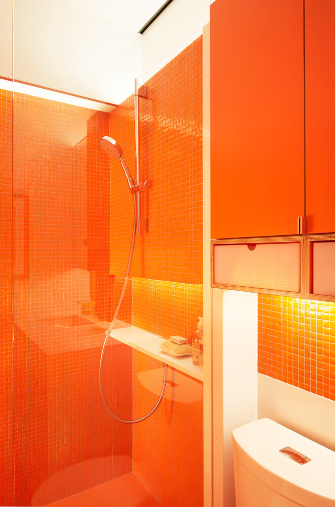The bathrooms are colour blocked, one in yellow, the other in orange. The designer used miniature molten mosaic tiles from Trend USA in both rooms.