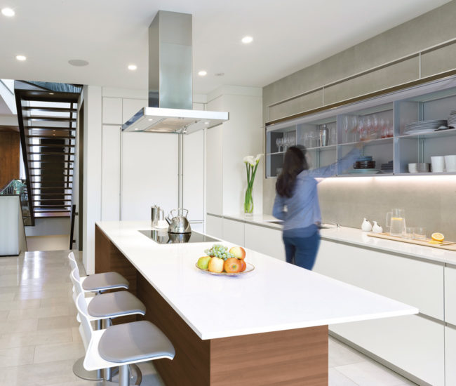 Loire limestone flooring by Stonetile runs through the kitchen and living room areas. Kitchen system by Valcucine.