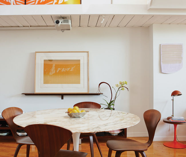 In the dining area is a marble-top Saarinen table with Cherner chairs, all from Quasi Modo. A screenprint by Ed Ruscha is propped on a picture ledge.