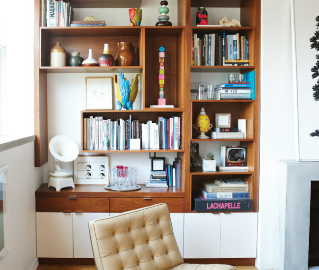 The bookcase contains a number of artworks including a talking stick by Douglas Coupland (centre) and Science & Son's ceramic Phonophone. Neon sculpture by Kelly Mark.