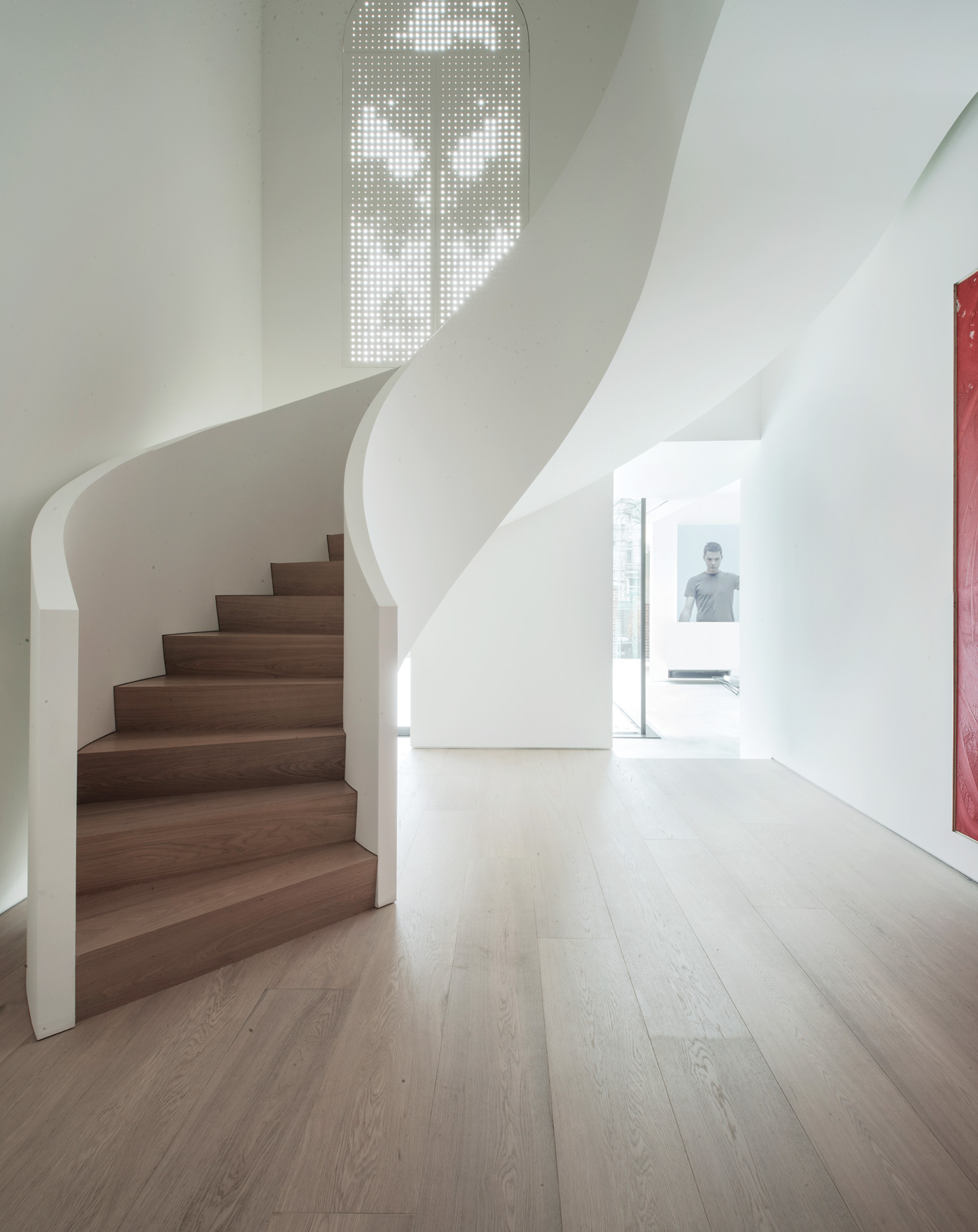 A perforated screen covers the second-floor window, so as not to distract from the commanding stairway.