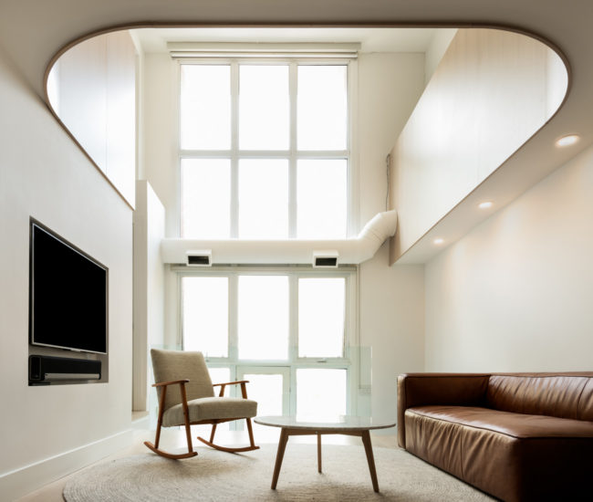 A view of the church conversion loft from the west-facing patio reveals its 3.6-metre-long curved wall element. Sofa, pouf, coffee table and rug by Article.