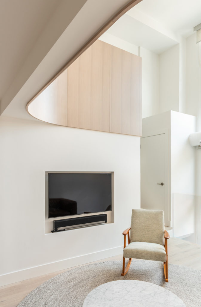 White oak flooring throughout matches the curved wall element and warms the otherwise all-white space. Rug from Article; the armchair is a vintage find.