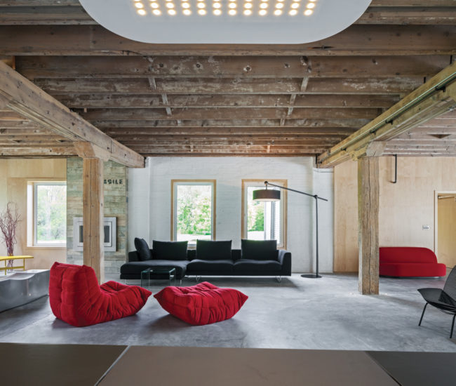 Virtually wall-free, the main level is now used as a living area and kitchen. Sofa by Jesse, seat and ottoman by Ligne Roset, LED pendant by Fontana Arte.