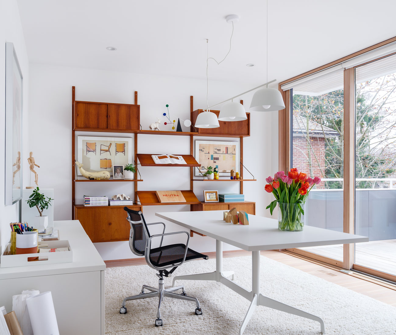 In the office, a sliding glass door from Kolbe Windows & Doors leads to an upper balcony. Muuto lights from YLighting; Eames desk and chair from Herman Miller; vintage teak media unit from Filter.