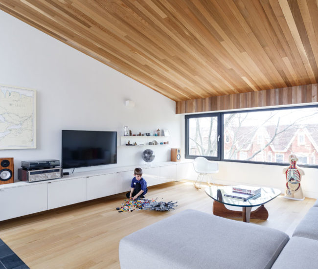 The angled, cedar-clad ceiling is a fitting choice for the third floor living room, a treetop retreat for the family.Sofa, coffee table and Eames chair from Quasi Modo; sconces from YLighting. Photo by Arash Moallemi.