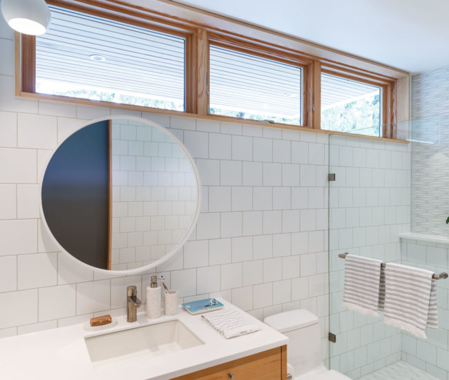 A round mirror contrasts with the linear details in the bathroom.