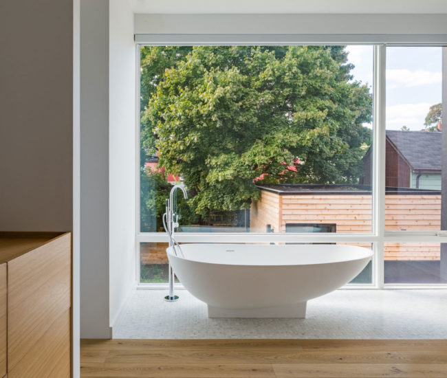 The master suite includes this bathtub, overlooking the lush yard.