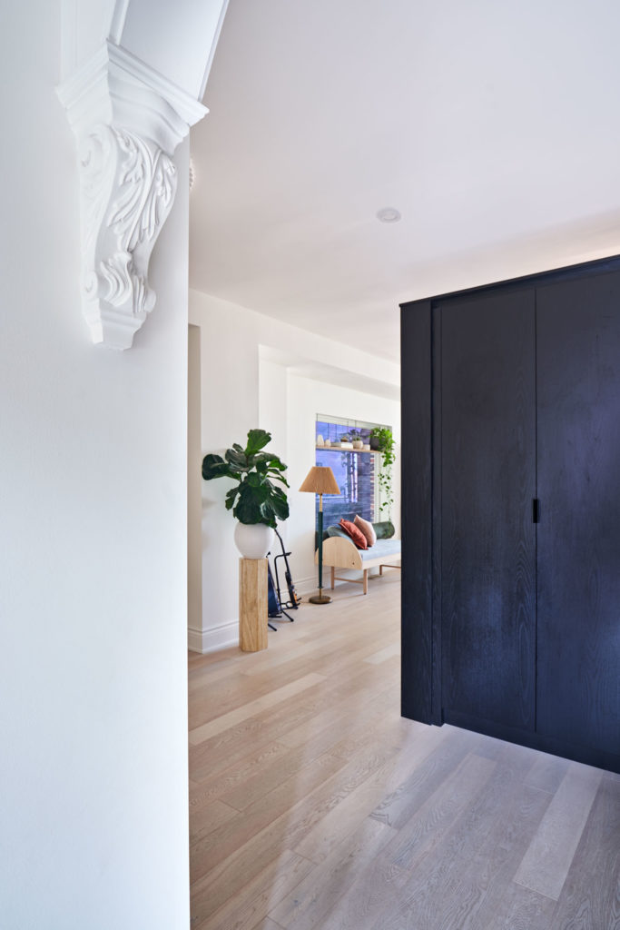 """Through the archway in the foyer, complete with believable """"Victorian"""" mouldings, guests are greeted by a two-metre-long wardrobe built by Twin Kitchen Canada."""