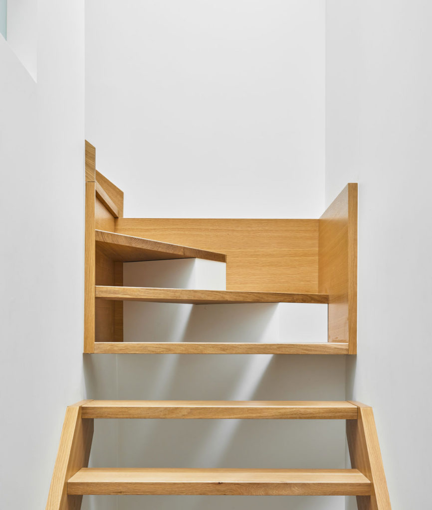 The staircase (built by LaFabrika) spans three storeys and features open white oak treads on concealed brackets. Neue Floors' white oak planks from Nadurra run throughout.