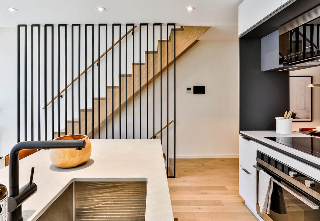 The railing, by Stainless Dimensions not only delineates the stairs from the kitchen but enhances the ceiling height.