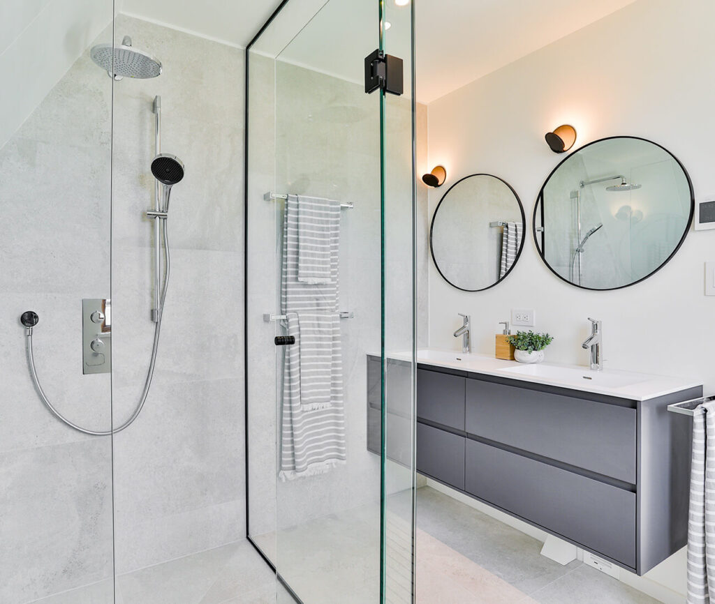 An all-glass shower enclosure by Tiqeq Homes takes centre stage in the master bath. Vanity by Muti; floor and wall ceramic tiles from Stone Tile; sconces from Casa Di Luce.