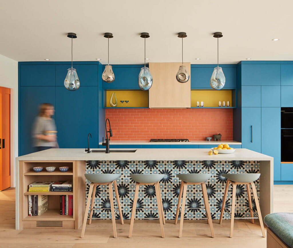 The island is clad in quartz from HanStone and backed by ocean blue millwork, orange subway tile, splashes of yellow and orange accents. Neutral elements, including wood shelving, black fixtures and Hay barstools, lend some restraint. The pendants are by AM Studio.