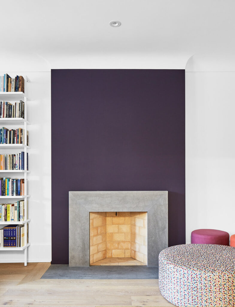 The fireplace was rebuilt to suit the new, sleeker space. A rich purple was used both to offset the home's bright palette, but also to match accents in its original stained glass windows.