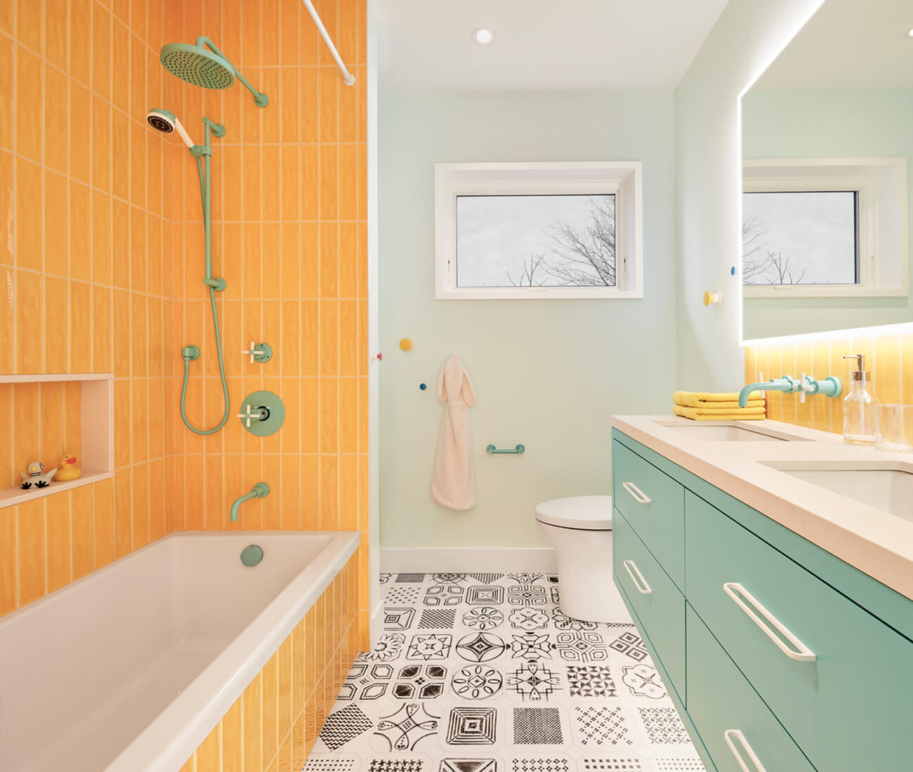 With pale teal and yellow, the kids' bathroom borrows from the bedrooms. Fixtures are by Rubinet Canada.