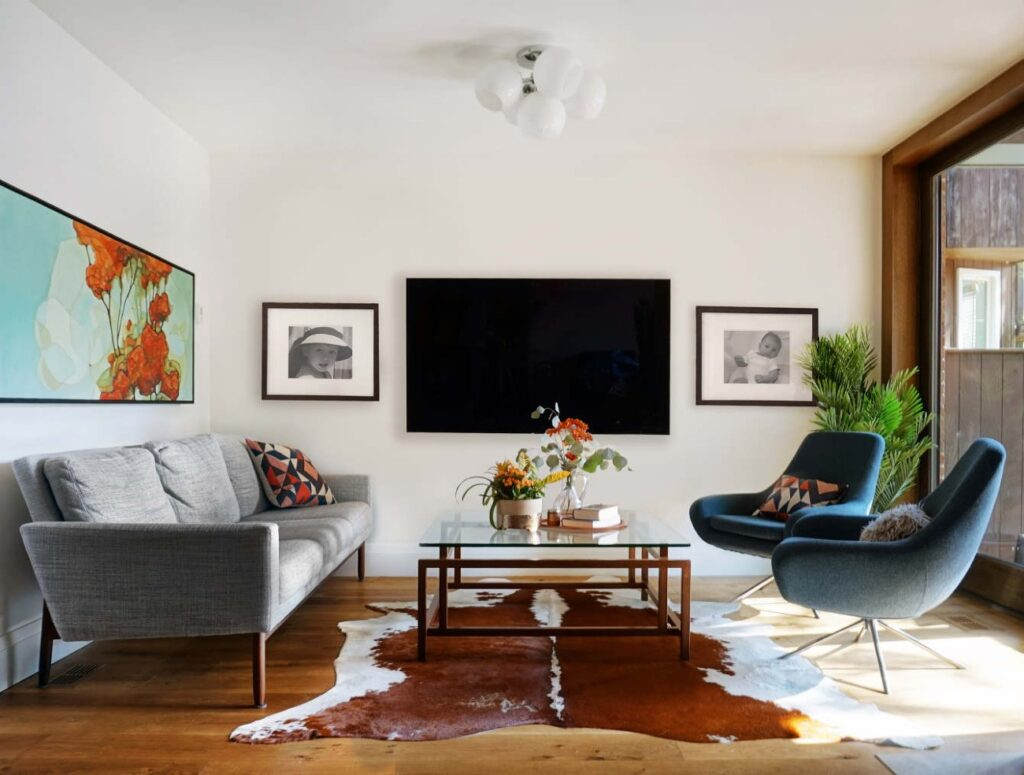 The living room contains a pair of distinct seating areas. The sofa is from DWR's Raleigh collection; the swivel chairs are by Noomi.